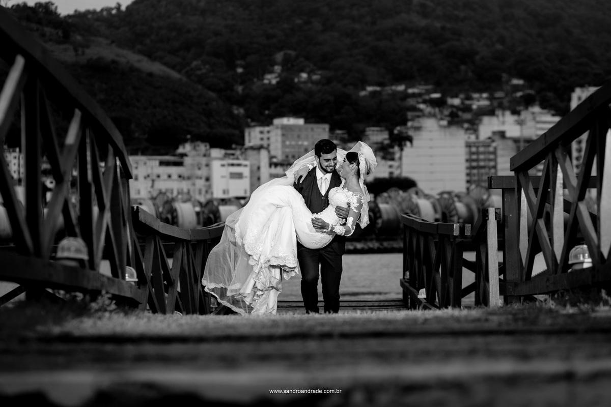 Apaixonado o noivo carrega sua esposa no colo e a olha com amor e ternura.