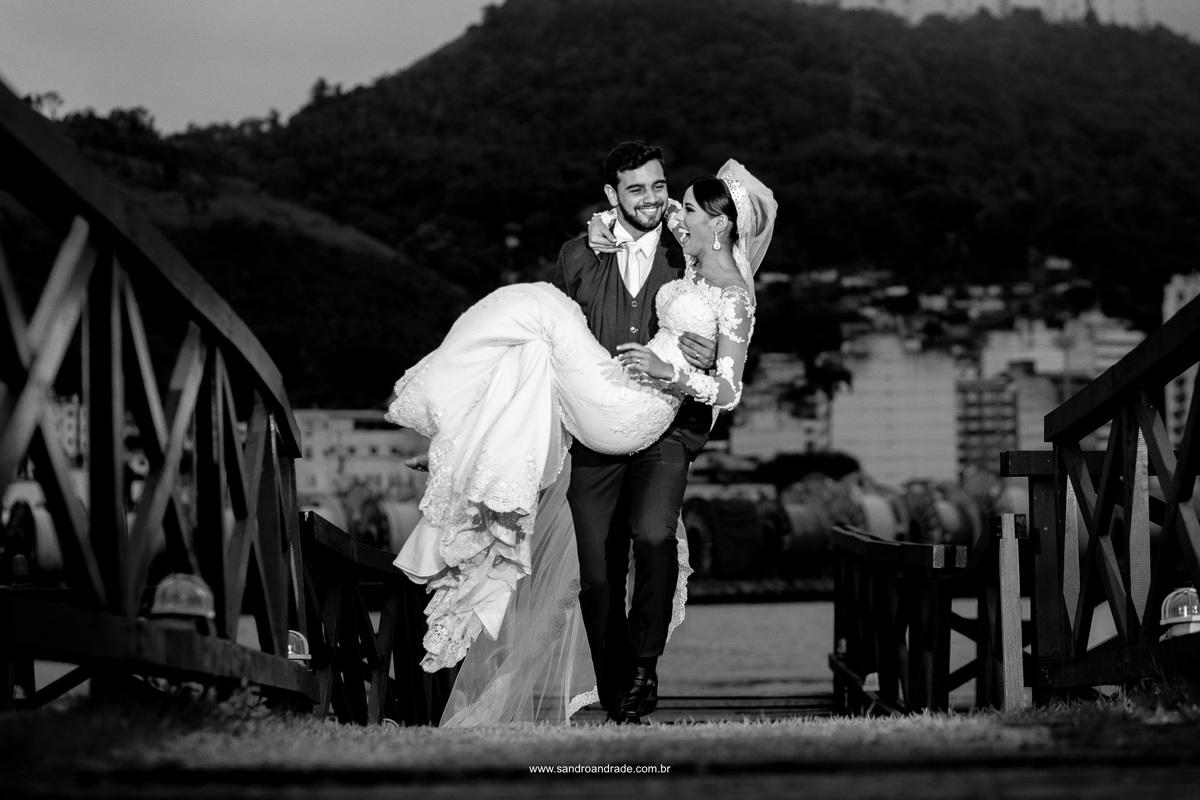O noivo carregando sua esposa em seus braços, felizes eles sorriem.