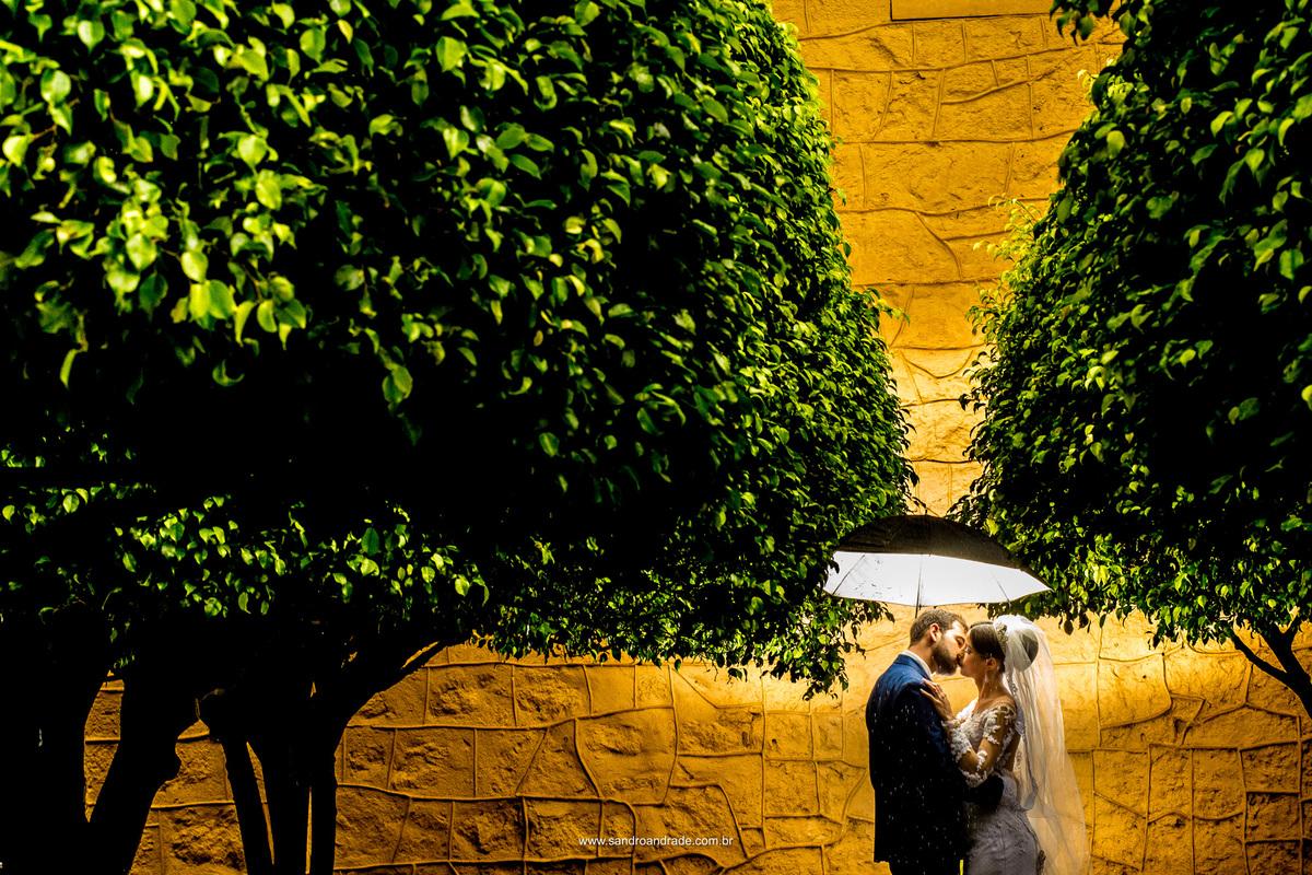 Em baixo da sobrinha eles se beijam, belissima composição desta fotografia de Sandro Andrade fotografo em bsb, sombrinha iluminada, arvores e uma parede amarela em contraste.