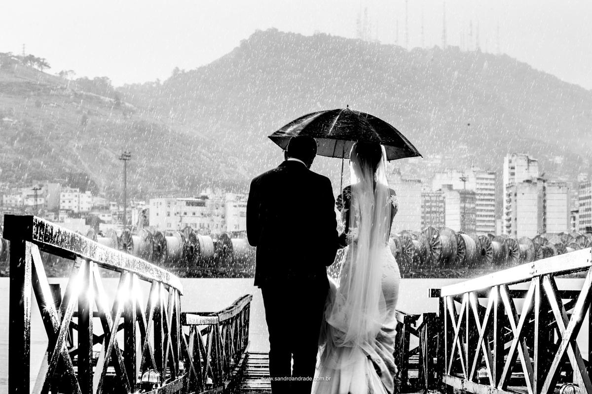 De baixo da chuva eles caminham até o meio da ponte, uma belissima fotografia em preto e branco e os pingos da chuva.