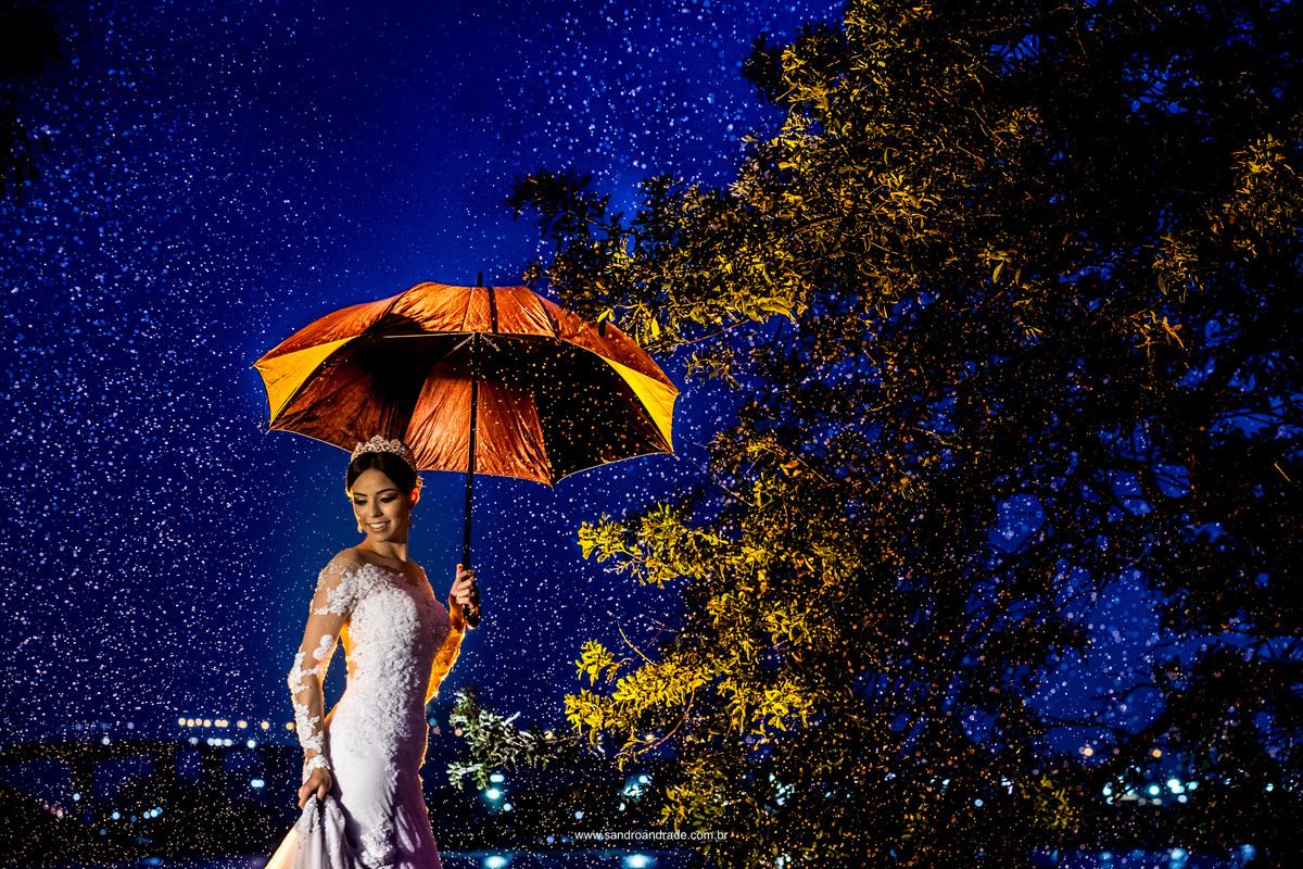 Colorido lindo nesta fotografia da noiva com uma sombrinha e muita chuva, luz de contra e cor como Sandro Andrade gosta.