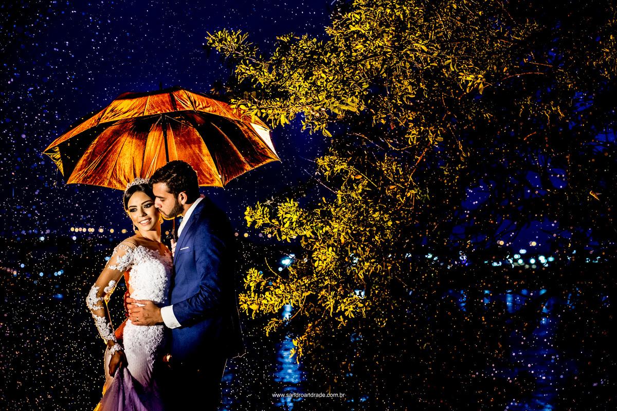 O esposo beijando sua linda esposa no rosto em baixo da chuva.