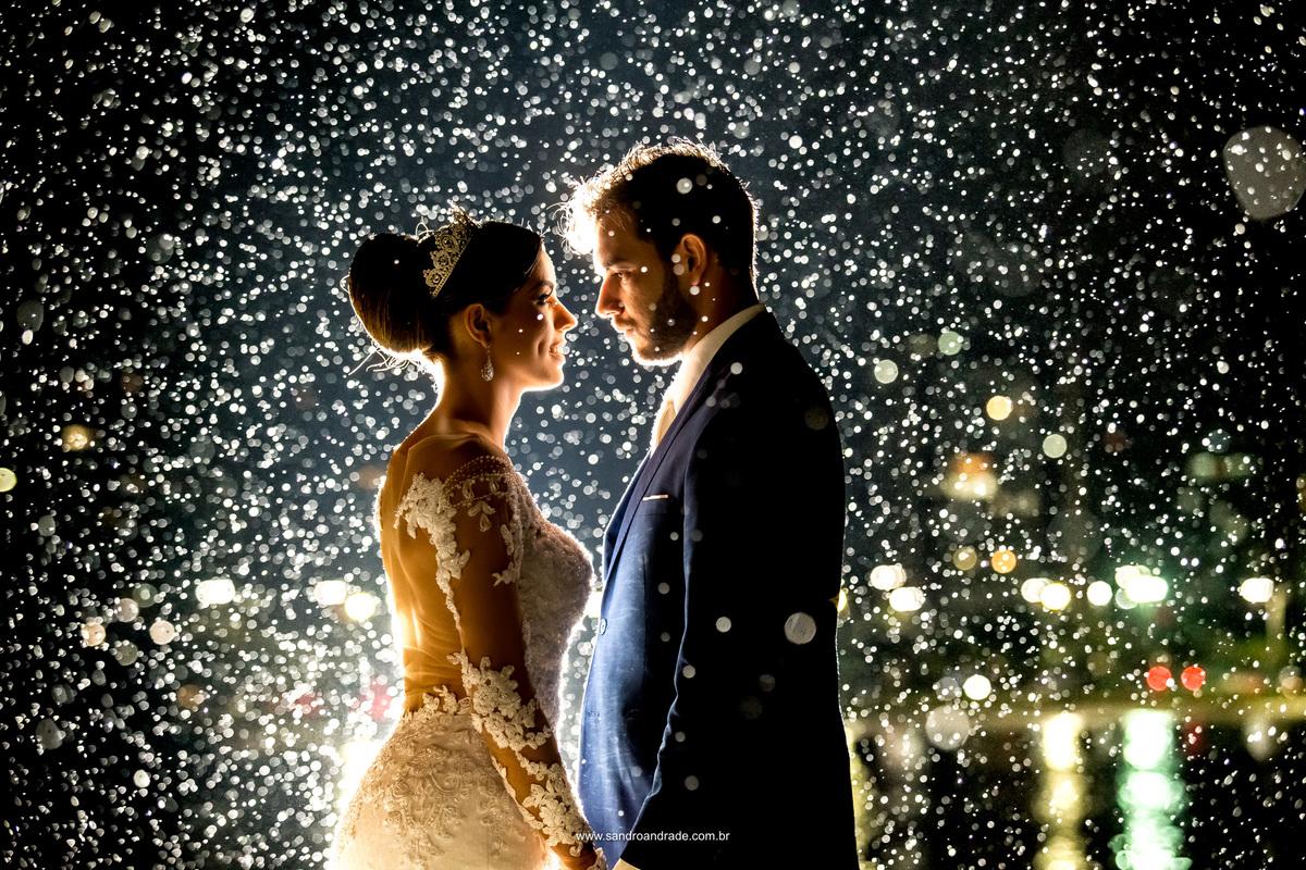 Retrato dos noivos na chuva, literalmente, sem sombrinha e um olhar apaixonado.