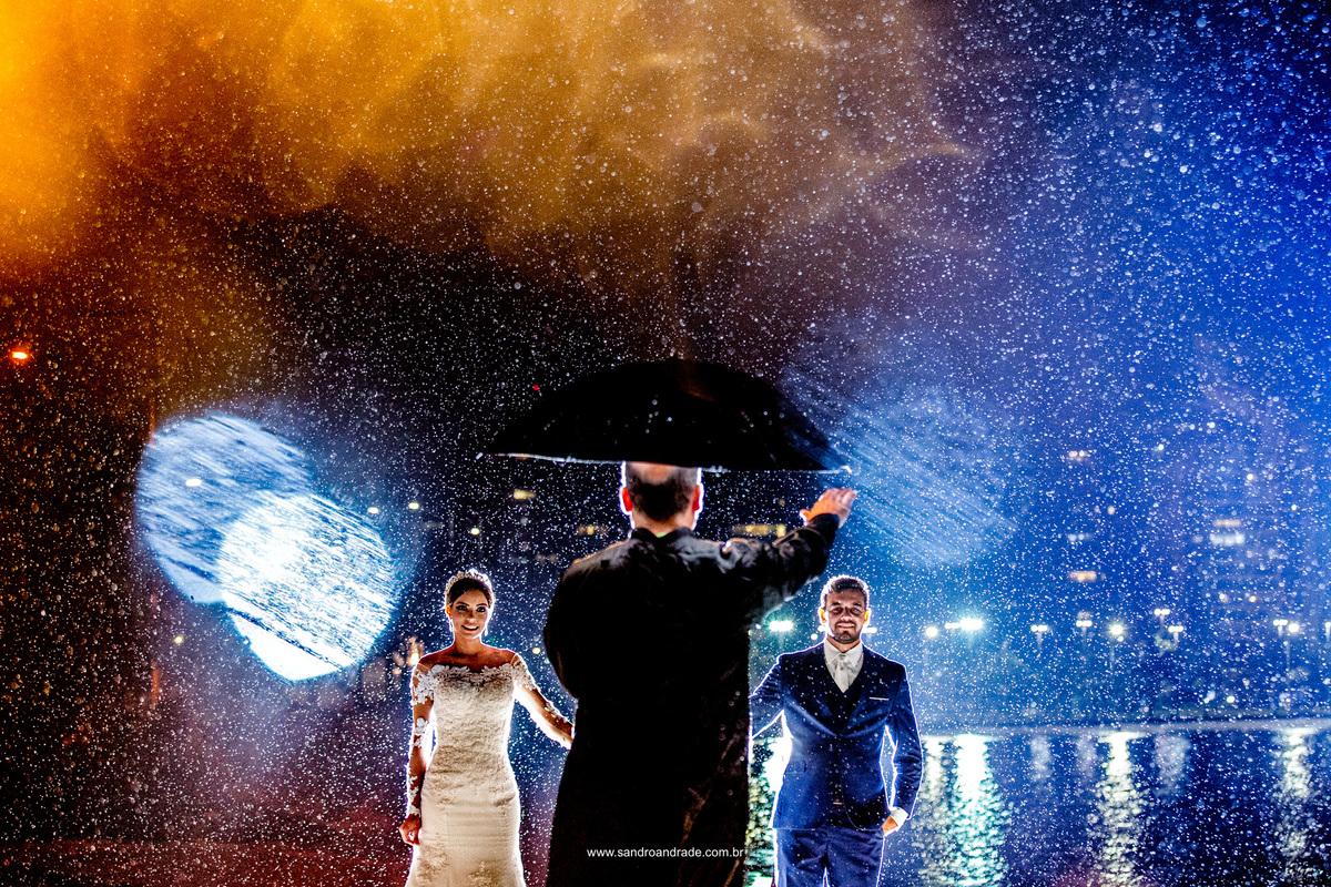 Fotografia artistica do casal e no improviso Sandro Andrade coloca uma pessoa igual um padre na cena, compondo como se fosse não um ensaio mas uma cena de casamento. O casal e o padre em baixo da sombrinha com luzes azul e amarela, boken e chuva.