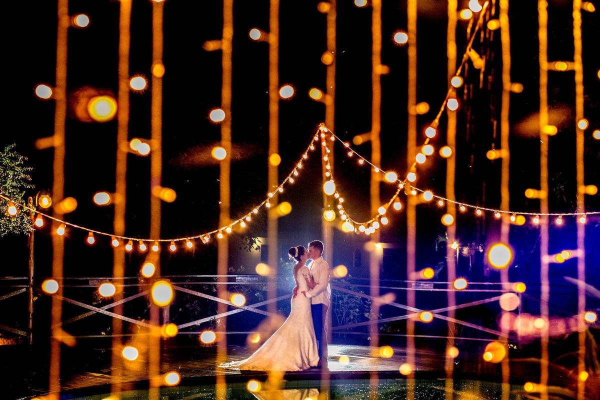 Uma linda fotografia colorida dos noivos para encerrar a festa, com uma dupla exposição com as luzes de led, a beira da piscina.