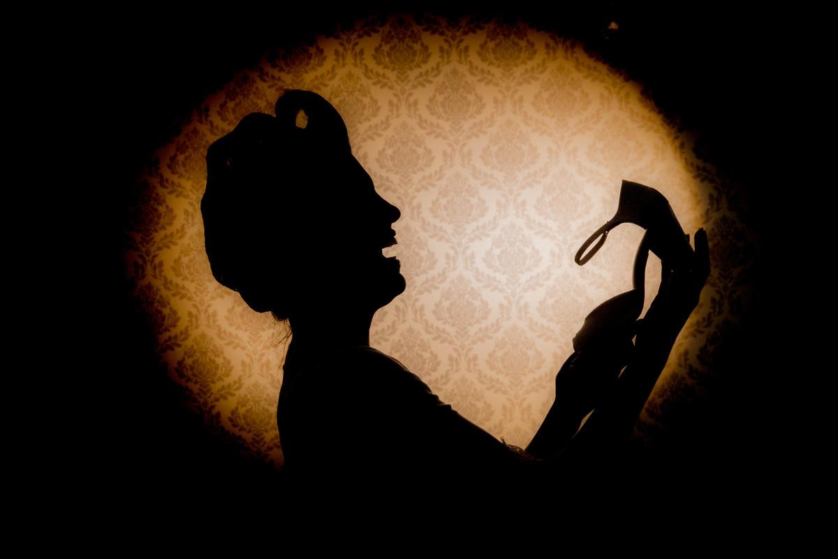 uma linda silhueta da noiva gargalhando com seu sapato na mão, fotografia criativa de Sandro Andrade.