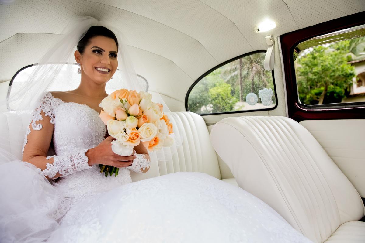 Dentro do carro, a noiva está feliz e com um sorriso irradiante.