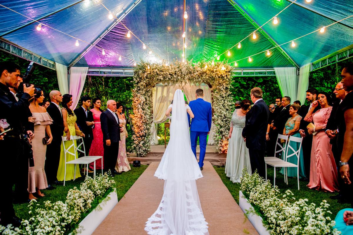 Chegada dos noivos ao altar, com madrinhas emocionadas.