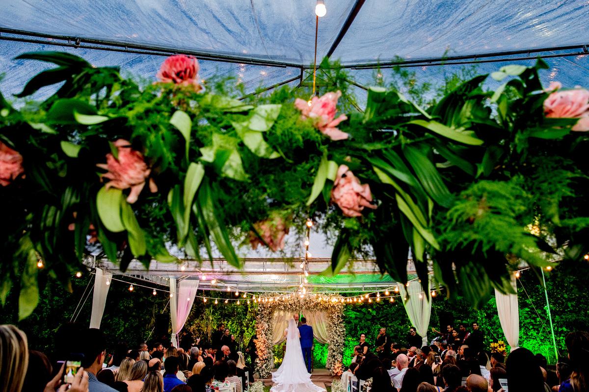 Linda fotografia de detalhe da decoração da cerimonia com os noivos de fundo no altar.