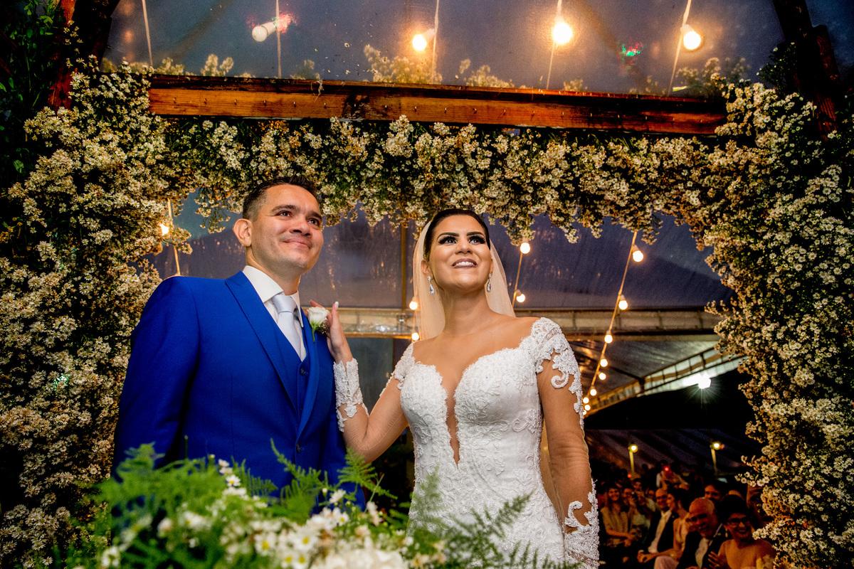 Felizes e agora casados, eles olham para o pastor, celebrante de uma cerimonia linda e divertida.