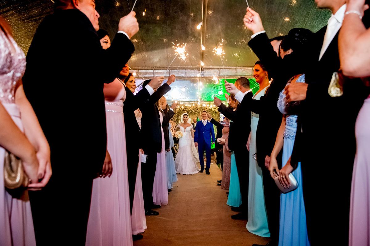 Saida dos noivos em um corredor feito pelos padrinhos e madrinhas