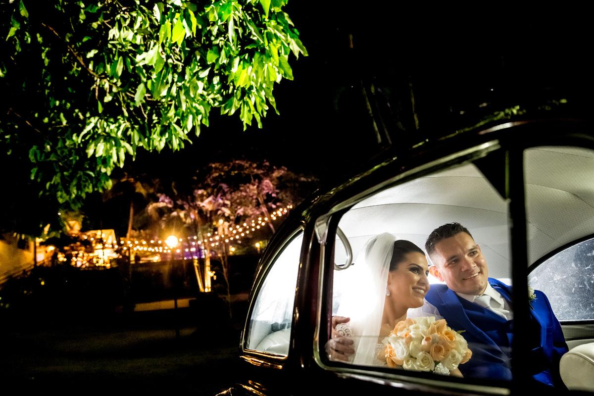 Os noivos no carro, chegando para a festa, feita no Cerimonial Cantinho da Pimenta.