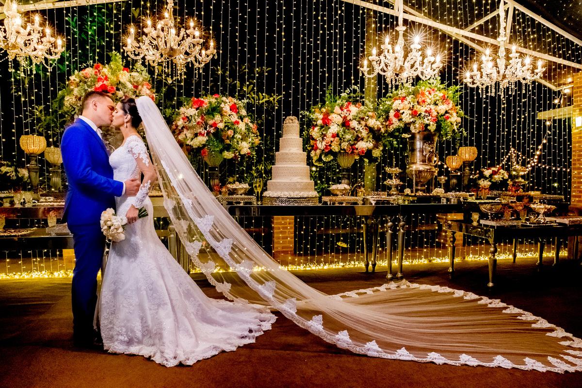 Lindos na mesa do bolo, com toda a decoração ao fundo eles se beijam.