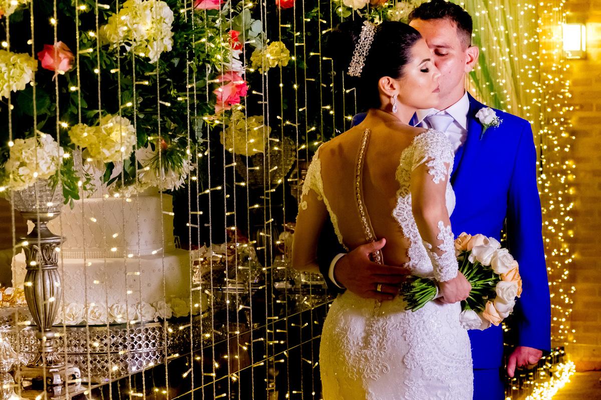 Fotografia linda dos noivos por tras da mesa do bolo, lindo gesto de amor, um beijo delicado.