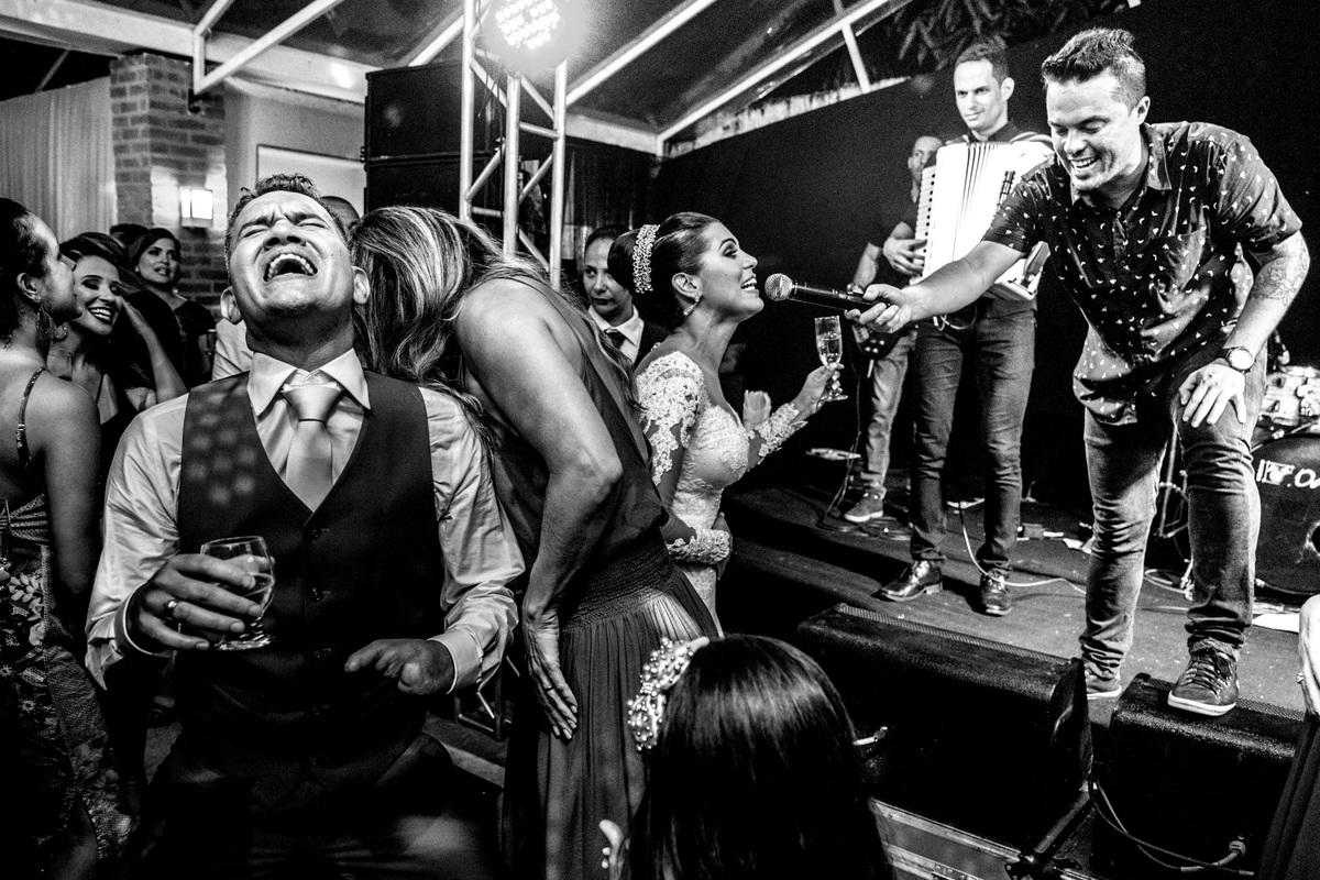 Fotografia de momento, por Sandro Andrade, a noiva canta no microfone de Romulo Arantes e banda e o noivo se acaba na boate.