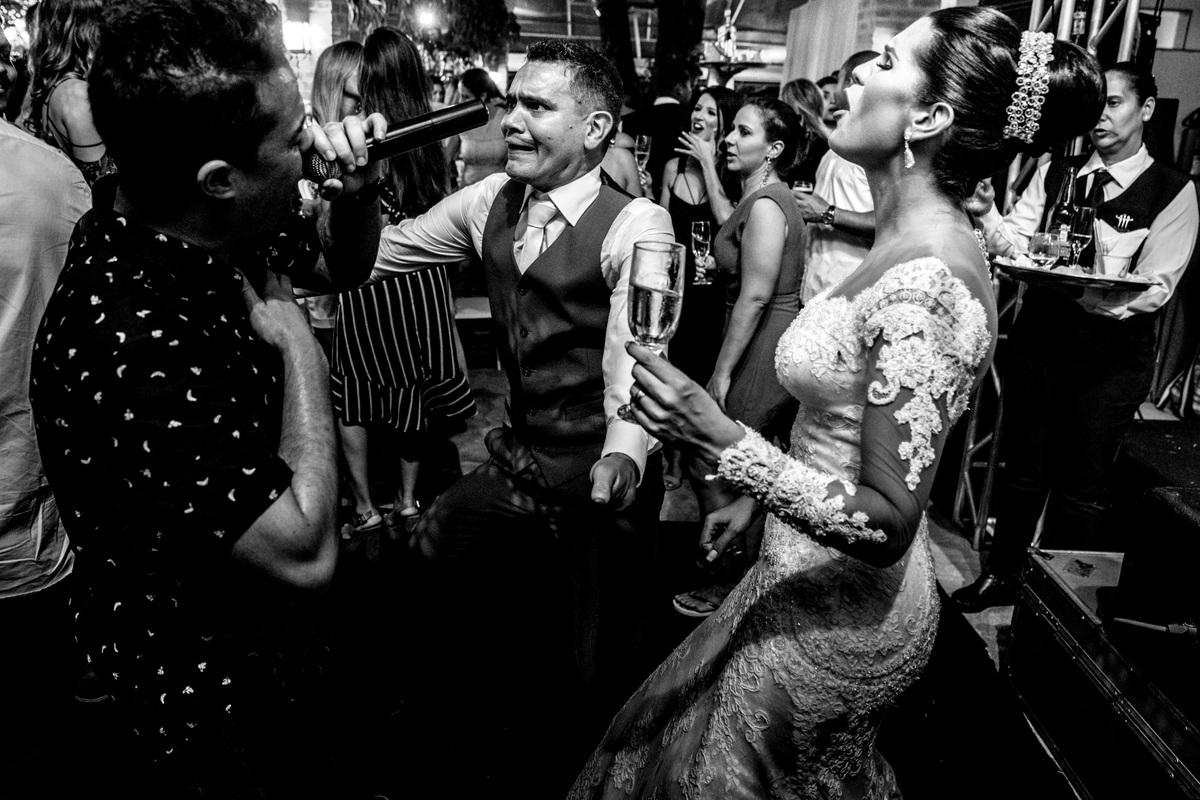 hilaria é a palavra para descrever a expressão dos noivos na boate, cantando juntos e com a banda. Fotografia de momento