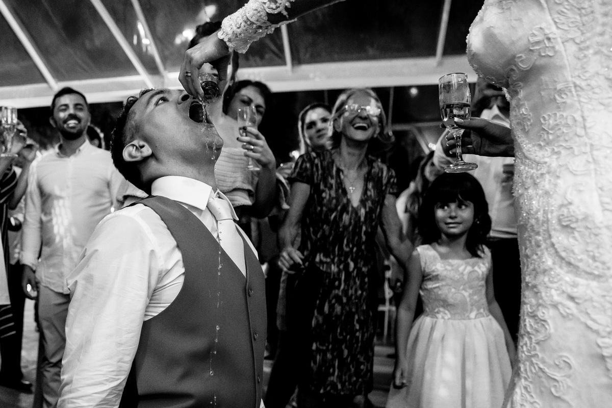 A noiva joga pinga na guela do noivo, enquanto os convidados observam