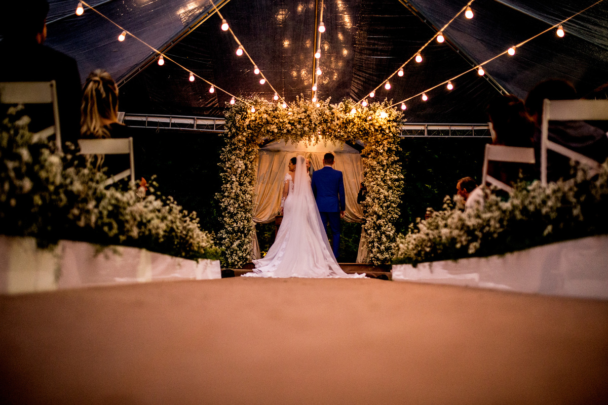 Uma linda fotografia dos noivos de costas no altar.