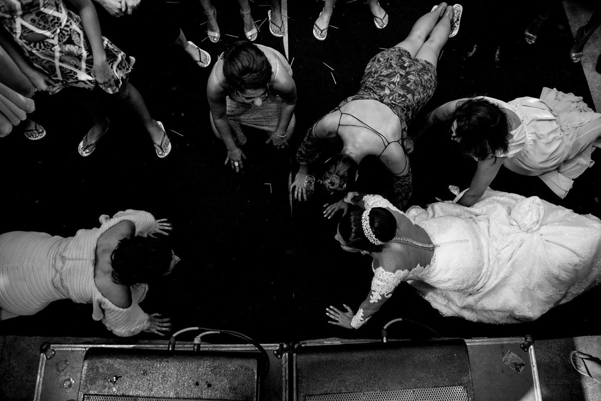 a noiva dançando com as amigas na boate do casamento, a dança incluia prancha no chão e de vestido de noiva ela foi até o chão