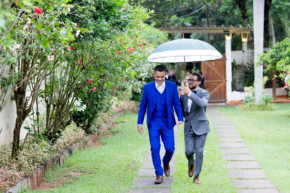 O noivo chegou, amparado por um amigo, o protegendo da chuva com um guarda-chuva.