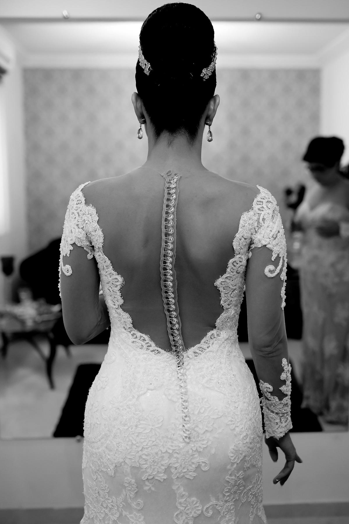 Costas do vestido de noiva e ao fundo a mãe dela se vestindo.