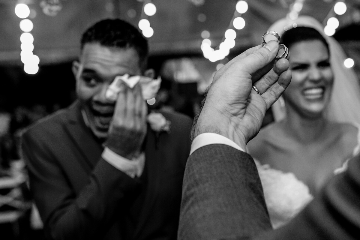 Com os noivos chorando de sorrir, o pastor apresenta as alianças aos noivos.