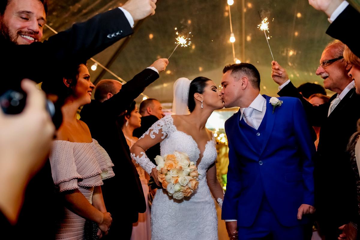Beijo dos noivos na saida, com detalhe lindo feito pelos sparkes.