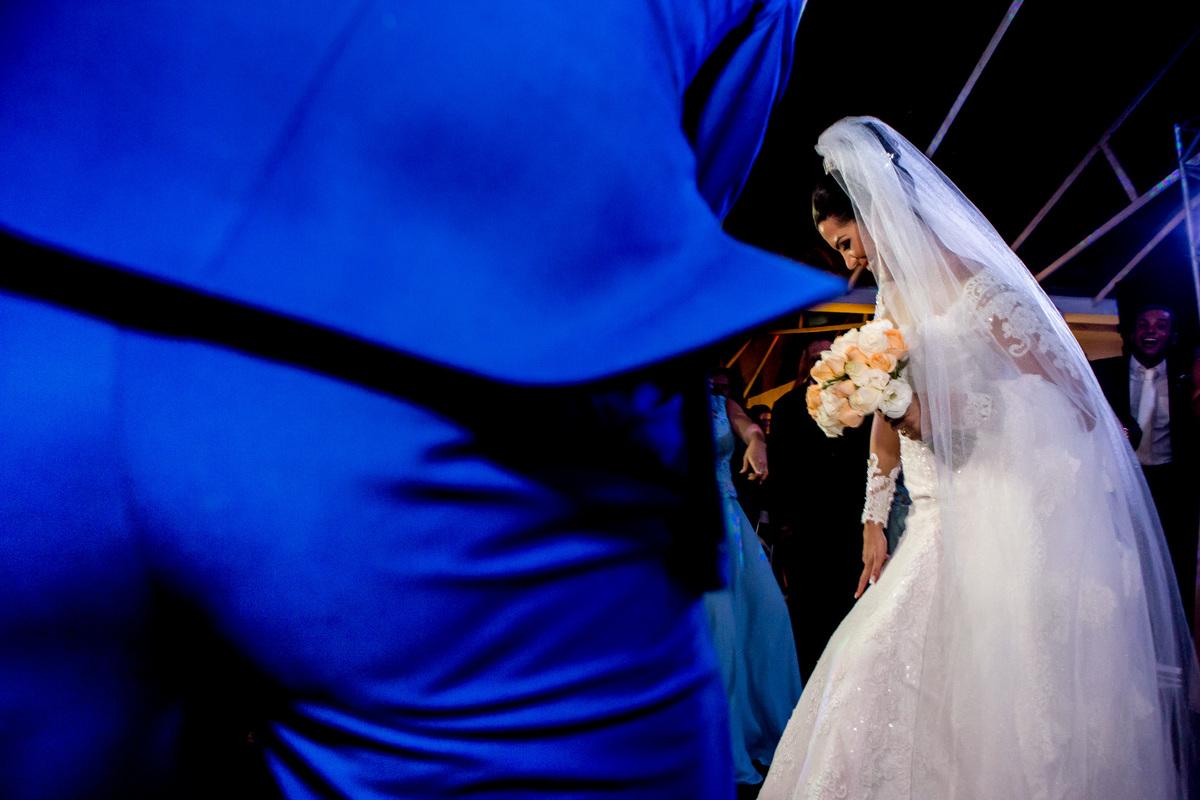 Com a mão no joelhinho e de vestido de noiva ela dança