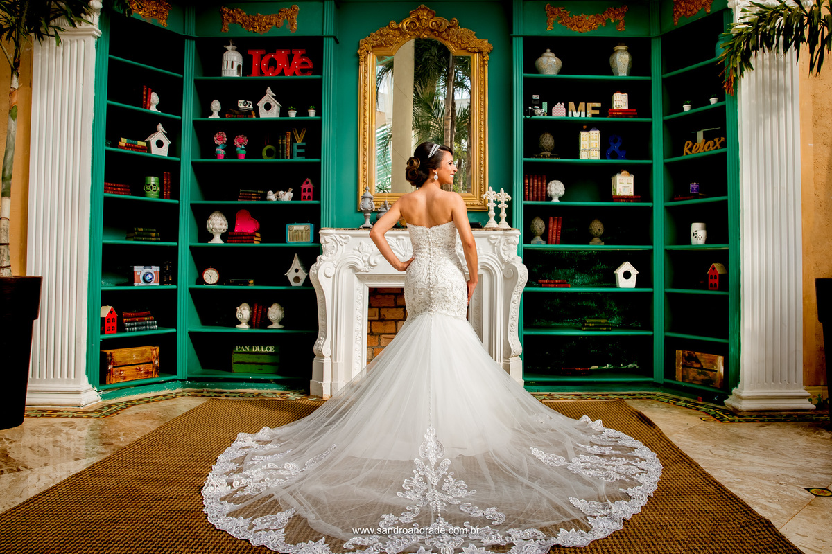 Uma linda fotografia da estante da Villa Giardini e a noiva muito bem postada no centro com seu lindo vestido todo aberto, pegando cada detalhe dele.