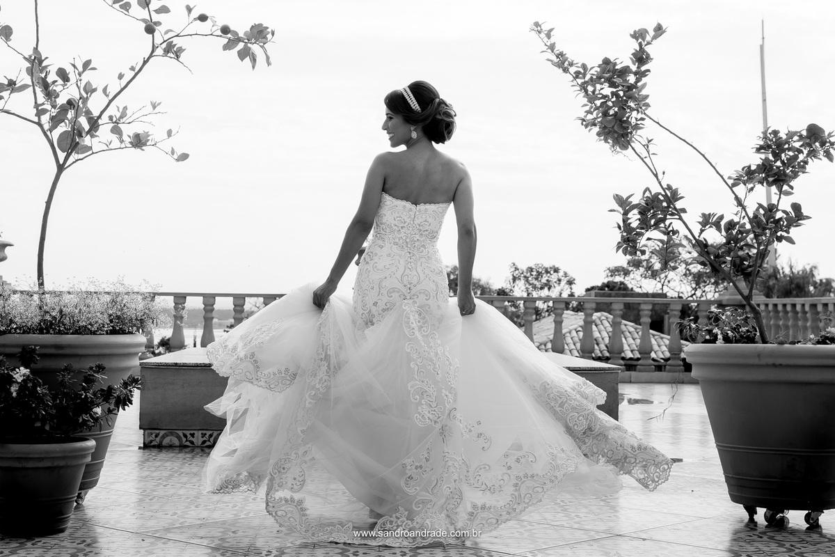 Linda e bela fotografia preto e branco da noiva girando e movimentando a saia do seu vestido de noiva.