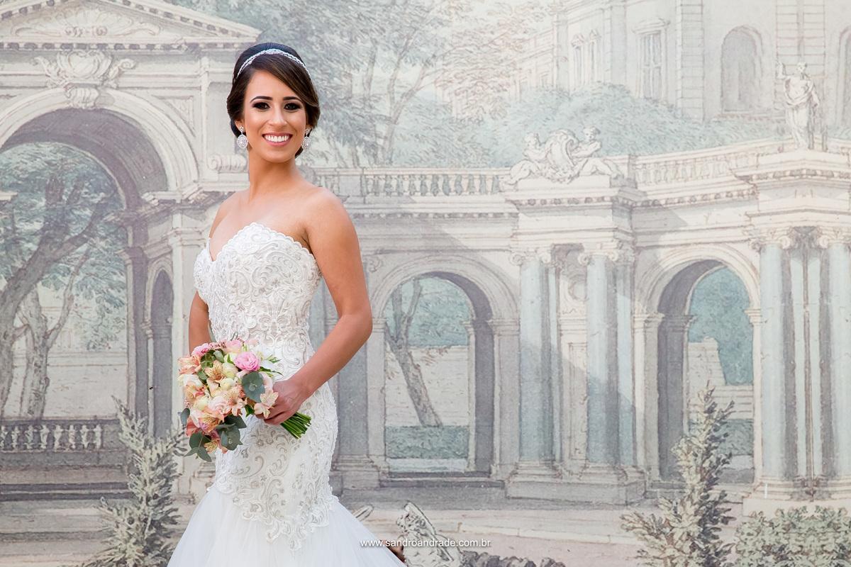 Um lindo retrato de noiva pegando o belo sorriso dela, detalhes do vestido e buque de noiva.