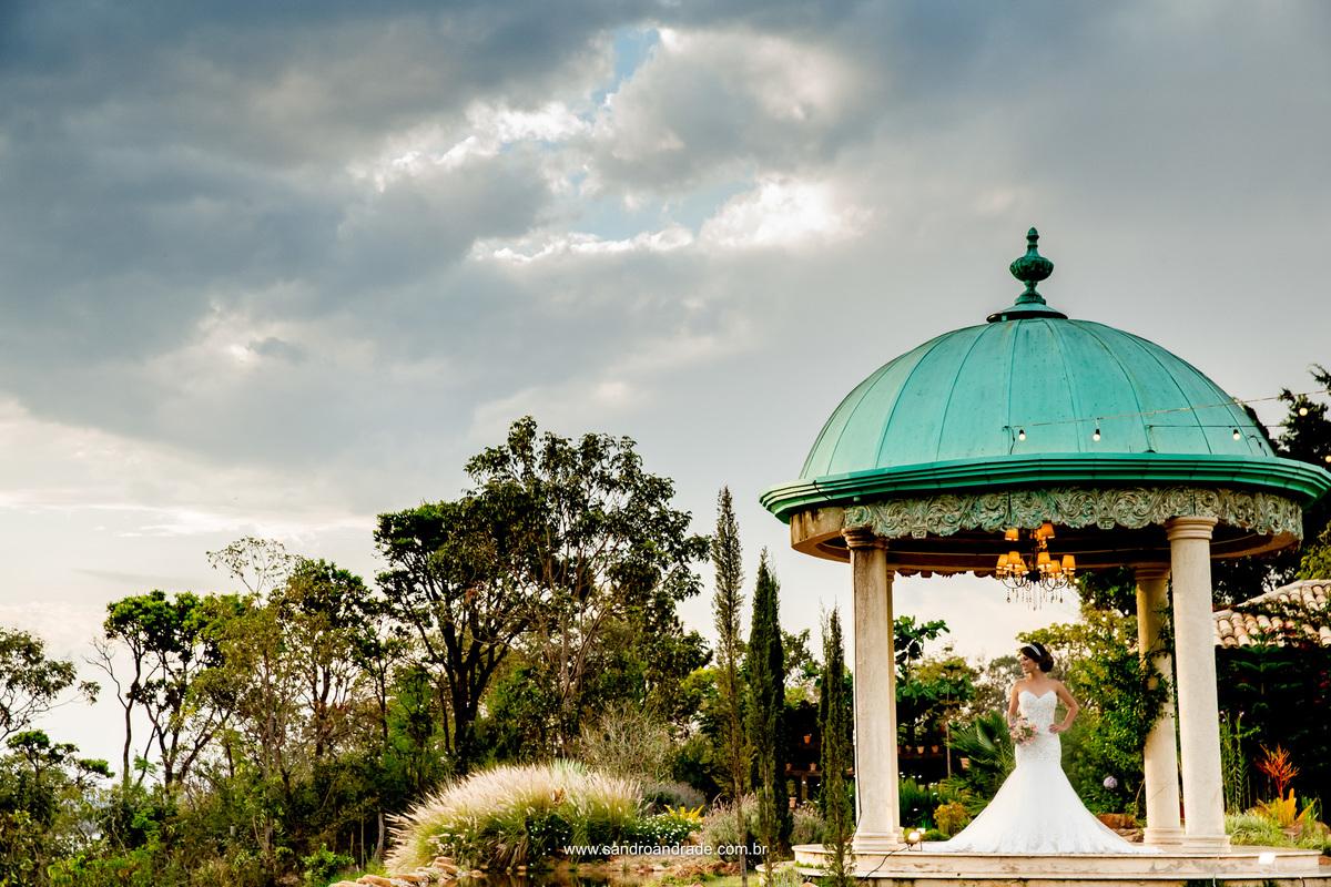 Uma imagem linda com um céu dramatico carregado de nuvens, o gazebo e natureza da Villa, com um belo trabalho paisagistico feito por Cauê Mauricio Giardini e a noiva toda glamurosa.