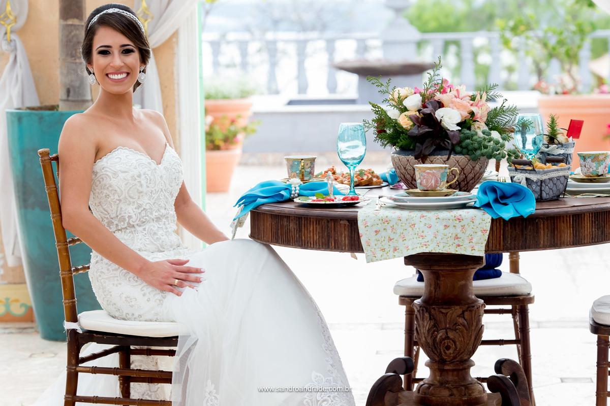 A noiva Milena posando para foto na mesa linda que foi montada para o chá da Milena.