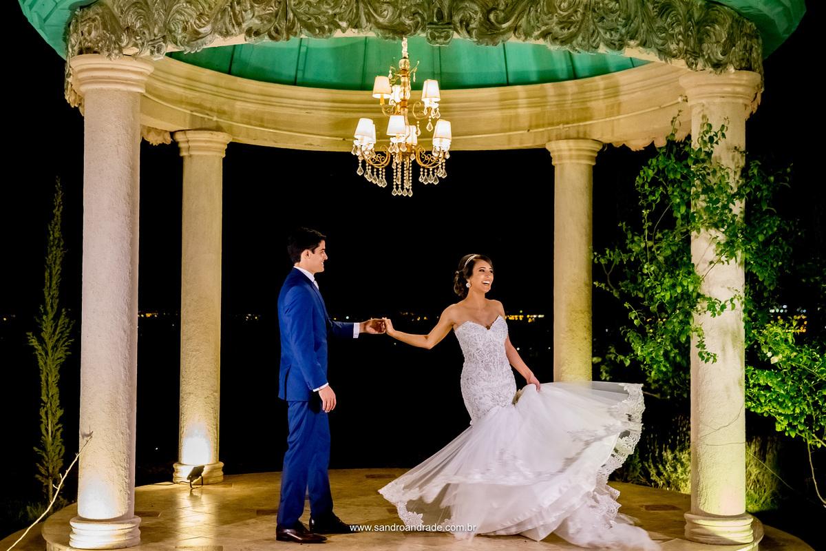 Lindos eles dançam no gazebo da Villa, vestidos por Maxime noivos e Black Tie em um lindo terno azul e ela em um belissimo vestido de noivas da Lá Fiancé. Fotografia criativa de Sandro Andrade, fotografo de casamento em Brasilia.