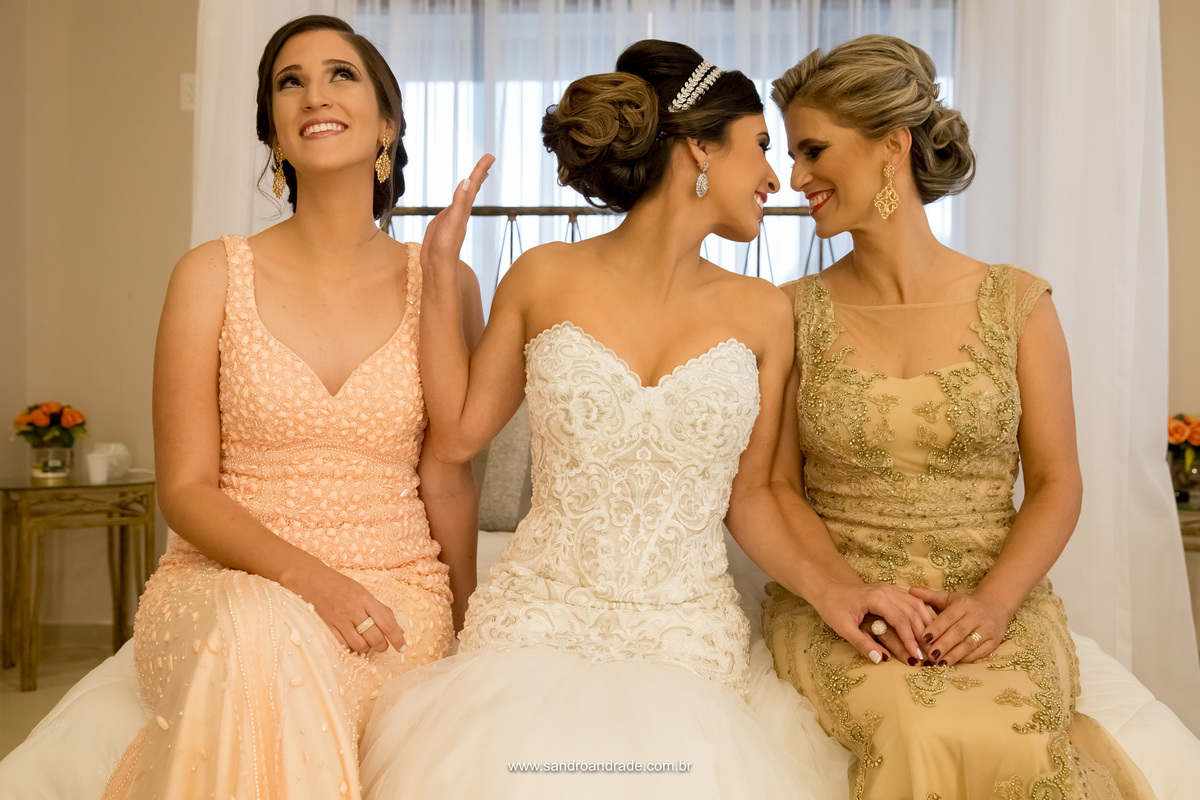 A noiva, sua mãe e irmã, sentadas na cama da suite, enquanto a noiva olha com um gesto de carinho para sua mãe, brinca com a irmã colocando a mão na frente, tipo sai pra lá, rsrsrs