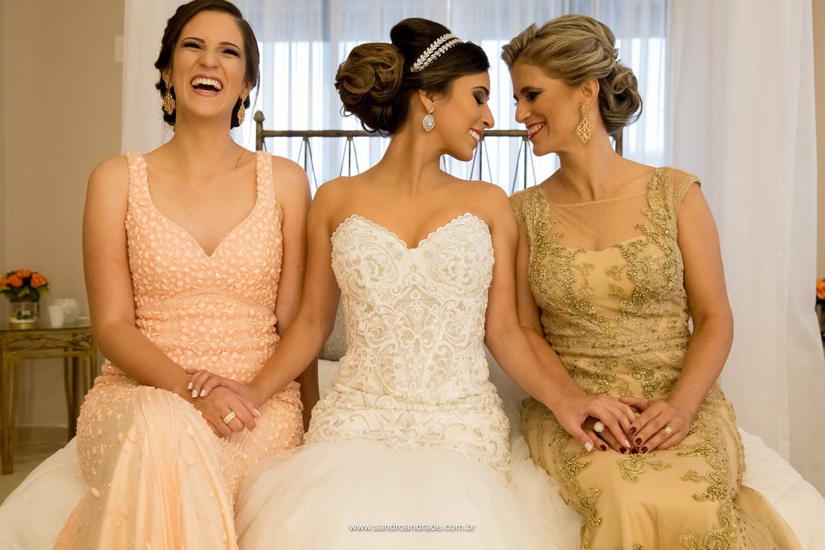 Rindo da brincadeira a irmã se diverte enquanto mãe e filha (noiva) tem um gesto de ternura.