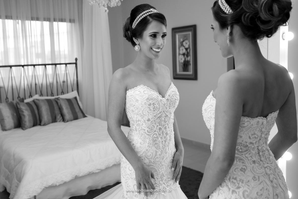 Ela está pronta, cabelo, maquiagem, vestido e acessórios, feliz se olha no espelho.