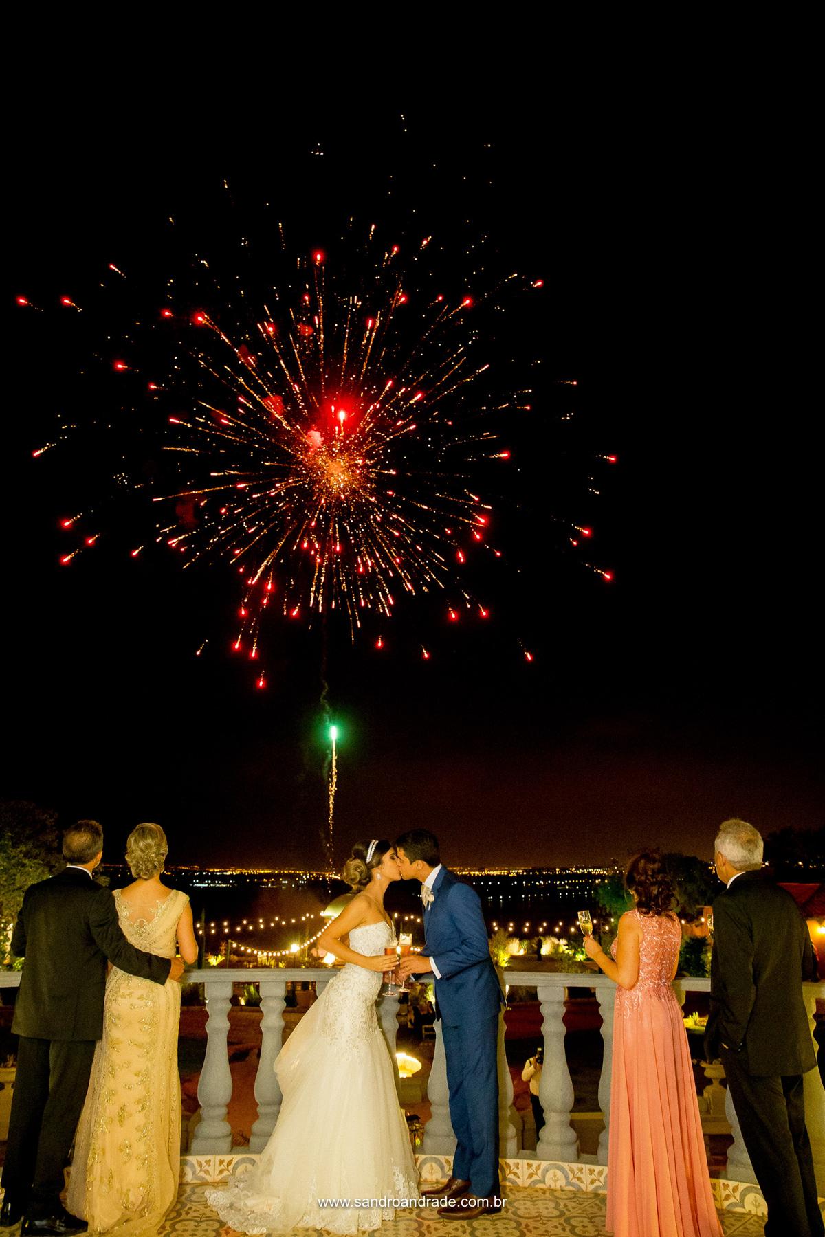 Os noivos se beijam em brinde com os pais enquanto fogos estouram no céu.