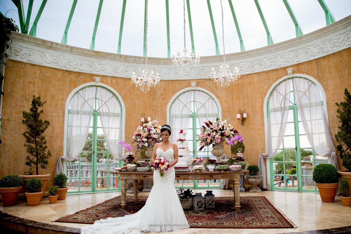 Fotografia da noiva na mesa do bolo, decoração por Dhyana Giardini, tudo lindo e de muito bom gosto.