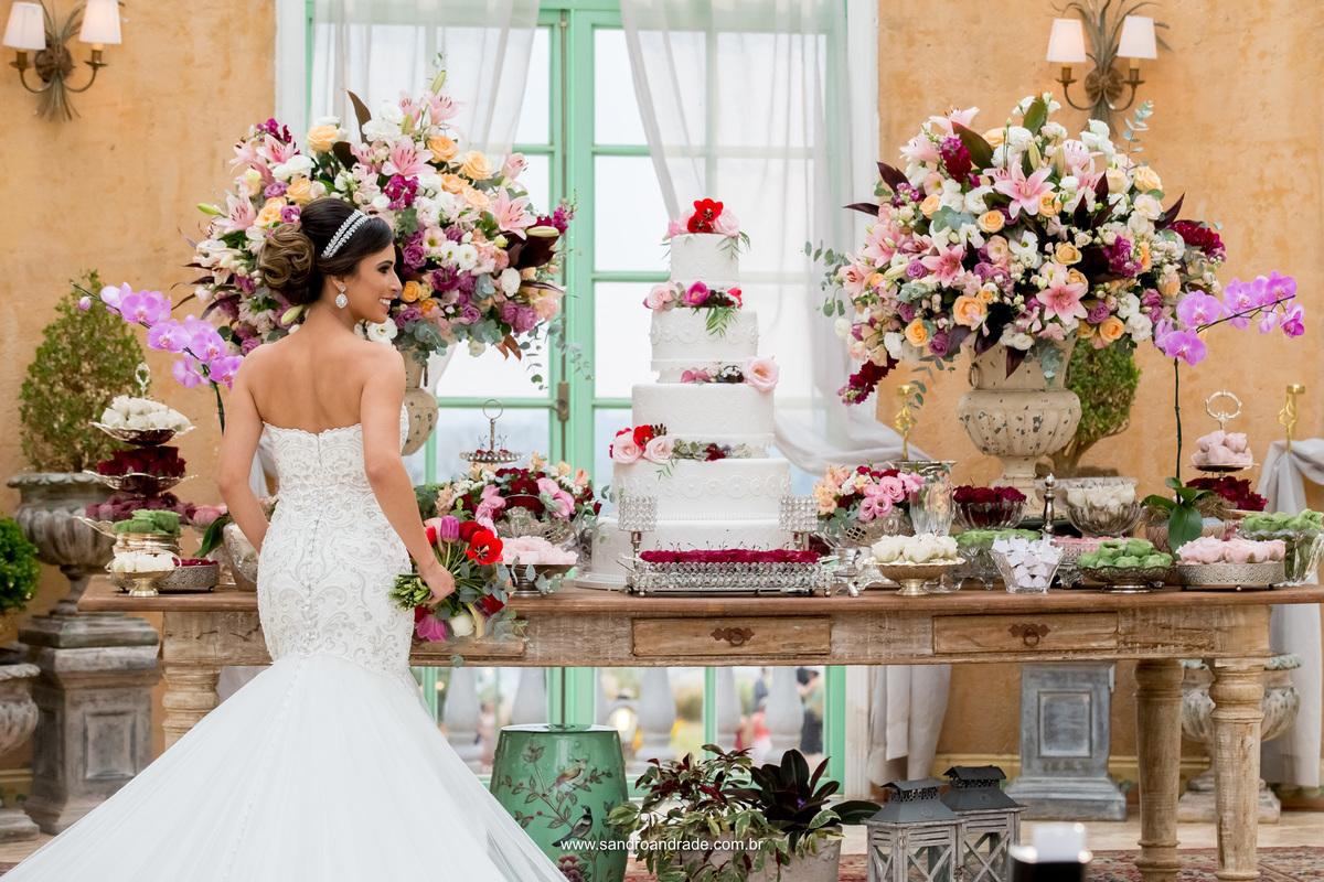 Linda ela posa de costas na frente da mesa do bolo. Maquete de bolo de casamento de Hiago Miguel.