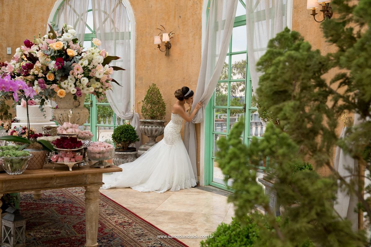 Linda e em composição com a decoração ela fica espiando por de tras da  porta de vidro, o noivo e padrinhos ja se posicionando para entrada onde será a cerimonia, no lindo gazebo da Villa Giardini.