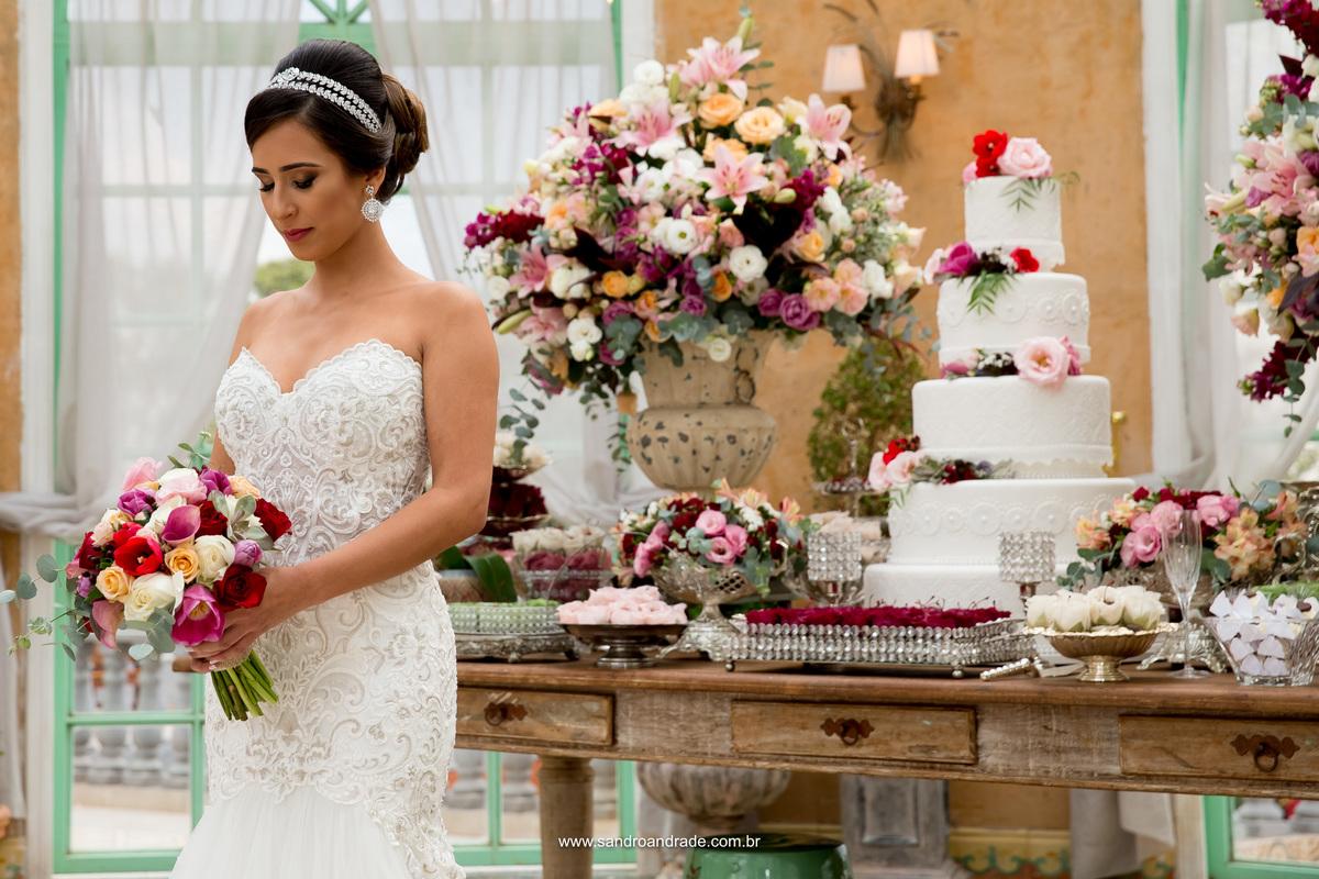 A posando para fotos na decoração, olhando seu lindo buque de noiva estilo bohô, tenddencia nos Estados Unidos.