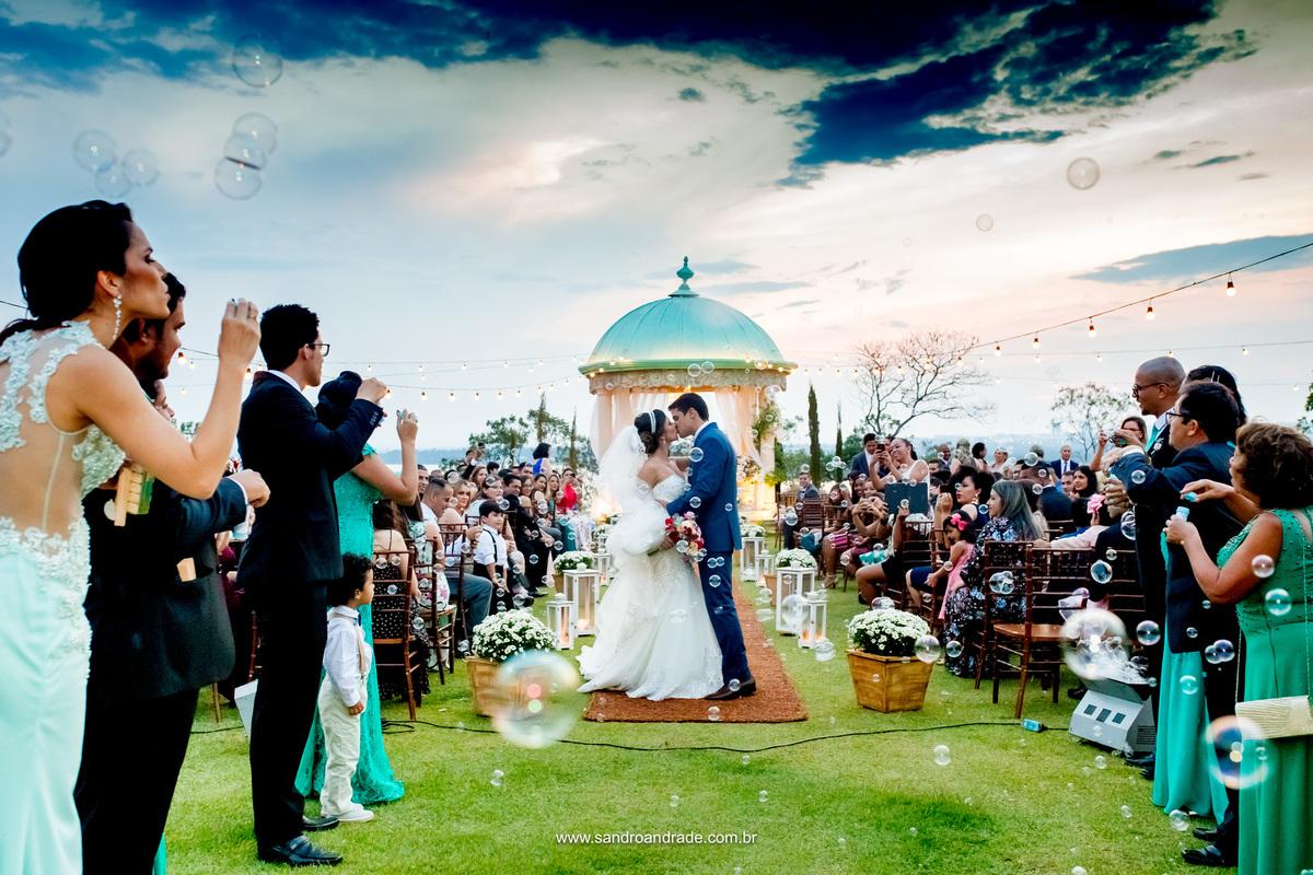 Na saída deles os padrinhos formam uma fila jogando bolinha de sabão, o noivo aproveita o momento e beija sua noiva, daqueles beijos de noivela.