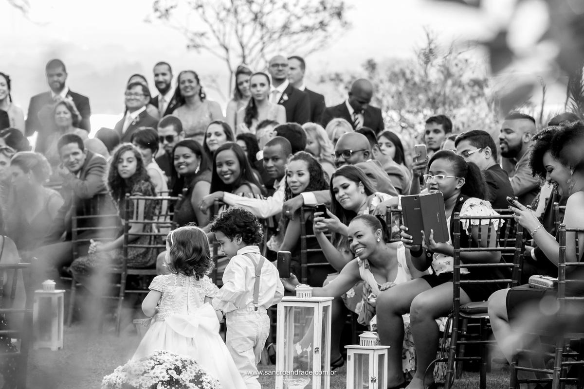 Fotografia linda em preto e branco feita por Sandro Andrade fotógrafo de momentos, da entrada dos pajens de tras, enquanto no detalhe todos os convidados os observa e sorriem com tanta fofura.