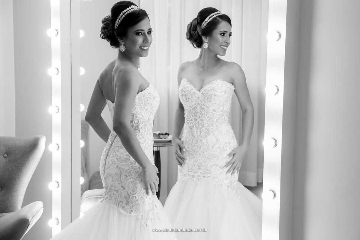 Ela está simplesmente linda, deslumbrante, uma fotografia preto e branco da noiva em frente ao espelho, sorridente e feliz.
