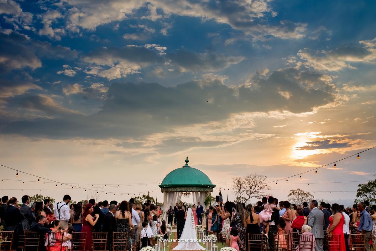 Quem vê este céu lindo nesta fotografia, não diz que 30 minutos antes estava chovendo muito, mas Deus ouviu as orações dos noivos, que oraram pedindo a Ele por um dia perfeito e debaixo deste lindo céu azul e por do sol ela entra com seu pai.