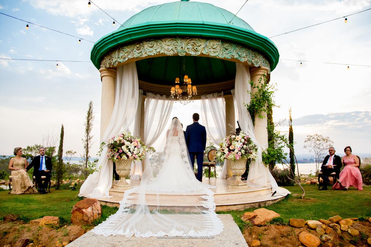 Foto dos noivos no altar com os pais na lateral do gazebo.