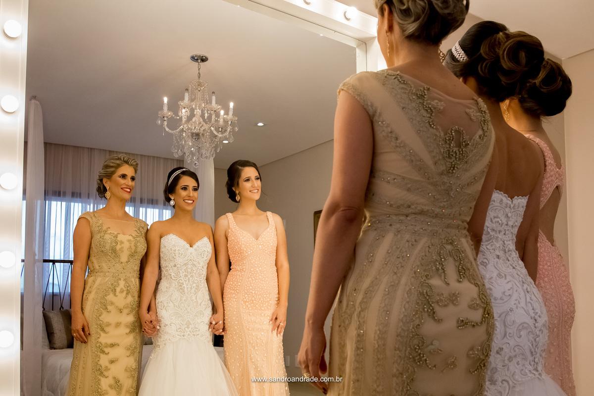 Prontas elas se olham no espelho, estão linda, mãe da noiva, irmã e a noiva.