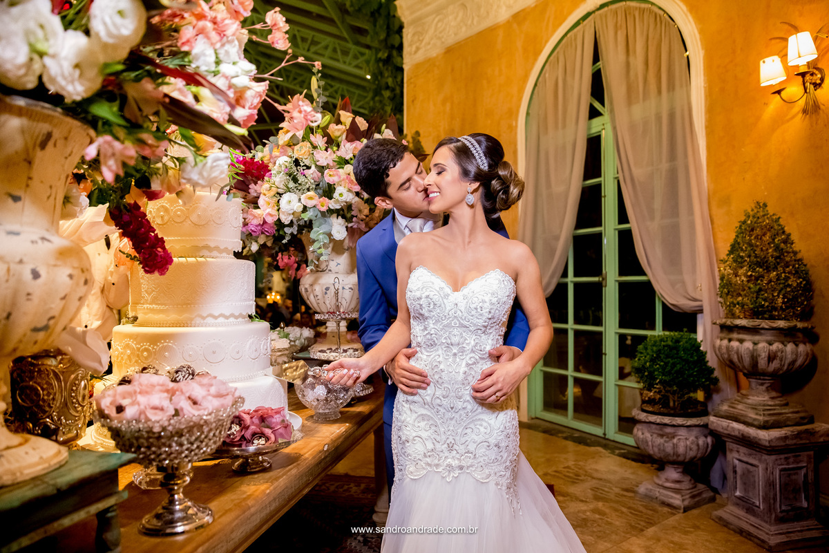 Os noivos cortando o bolo do casamento e o noivo dá um beijo delicado no rosto de sua amada