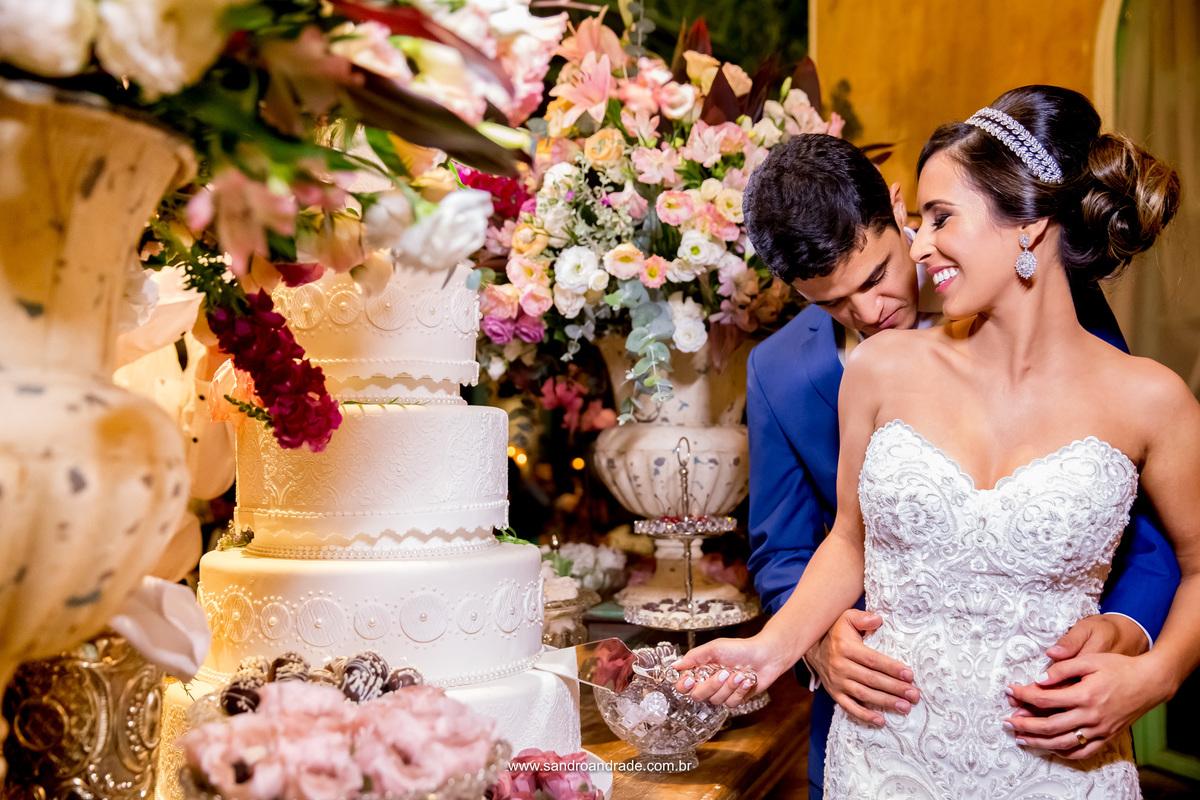 Felizes eles trocam caricias durante a sessão de fotos no corte do bolo, fotografia de Sandro Andrade fotografo de casamento em Brasilia.